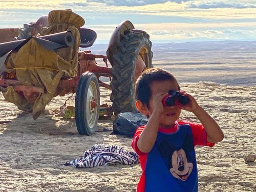 Hopi boy with new binoculars on top of cliff edge with tractor in background represents Hopi youth looking to the future and welcoming learning enrichment supplies during covid lock-down