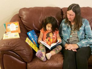 A young Hopi girl is reading a new children's book brought to her by Lainie Hoglan.
