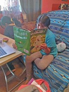 Hopi girl reading a book at home.