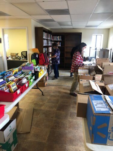 Village Services Coordinator Twila Gaseoma and Lainie Hoglan of Crossing Worlds Hopi Projects organizing and shelving first delivery of books March 24, 2021. Photo by Susan Henderson